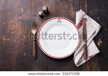 White empty plate and fork and knife on wooden texture background - stock photo