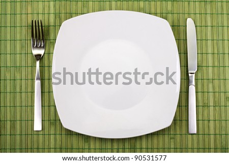 white empty plate, knife and fork served on table - stock photo