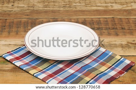 white empty plate on colorful napkin - stock photo