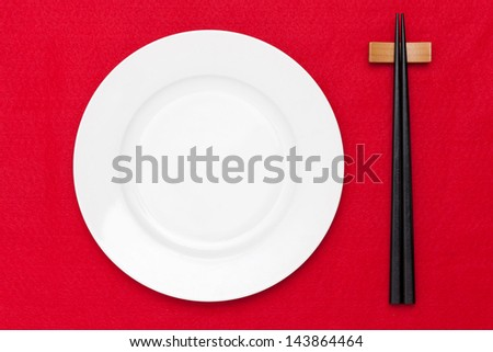 White empty plate with chopsticks on red table cloth - stock photo