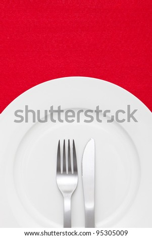 White empty plate with fork and knife on a red tablecloth