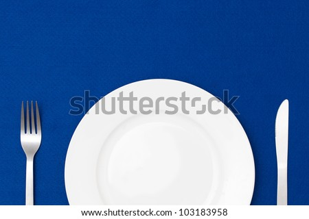 White empty plate with fork and knife on blue table cloth