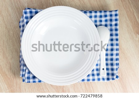 White empty plate with fork and spoon on wooden table