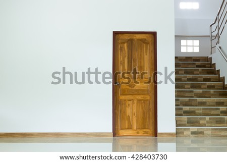 white empty room interior with wooden door and staircase - stock photo