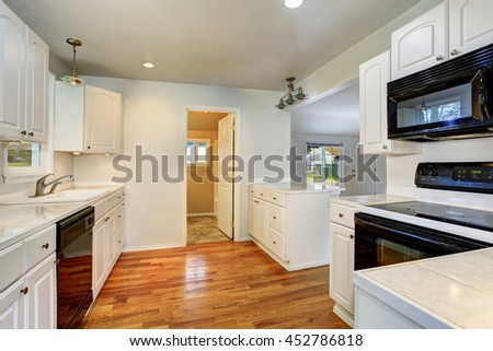 White empty simple old kitchen interior with hardwood floor and white cabinets in American historical house.