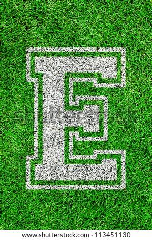 White english alphabet E on green grass - stock photo