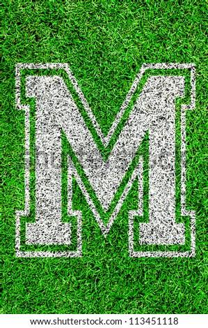 White english alphabet M on green grass - stock photo