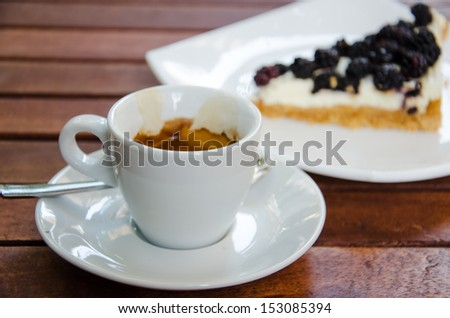 White espresso cup and a piece of blackberry cheesecake