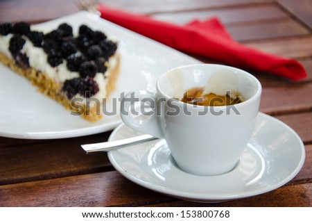 White espresso cup and a piece of blackberry cheesecake - stock photo