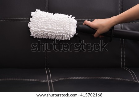 White fabric brush from steam cleaning machine being used on black leather couch - stock photo