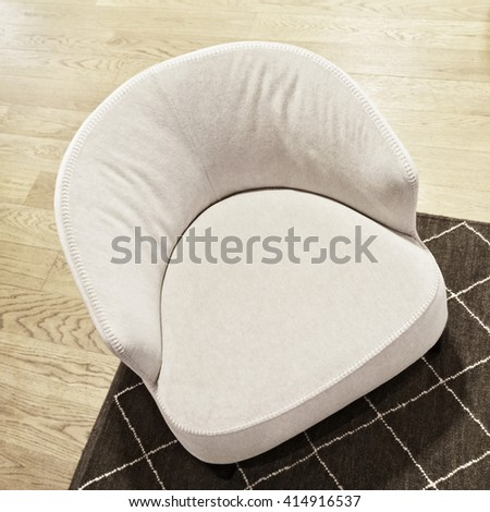 White fancy armchair on wooden floor. Modern style furniture.
