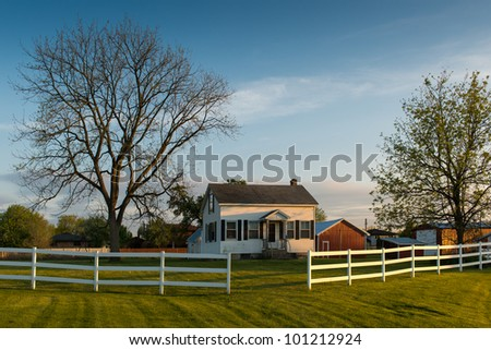 White farmhouse behind white fence in rural Illinois - stock photo