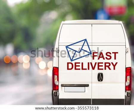 White fast delivery Van driving fast on city blurr bokeh street - stock photo
