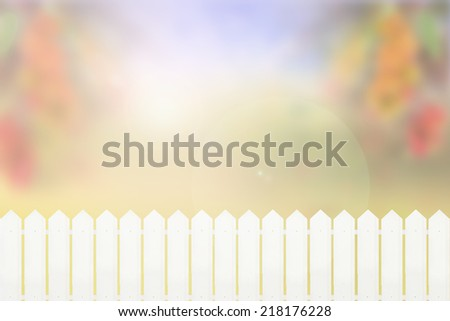 White fence and blurred colorful fruits garden