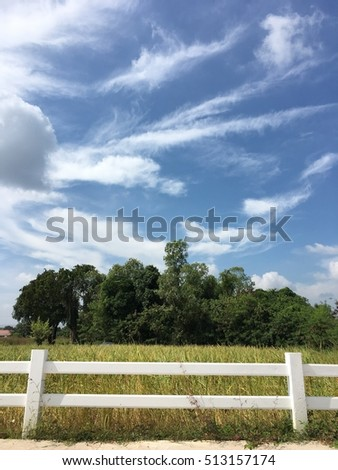 white fence at road side on blue sky cloud background