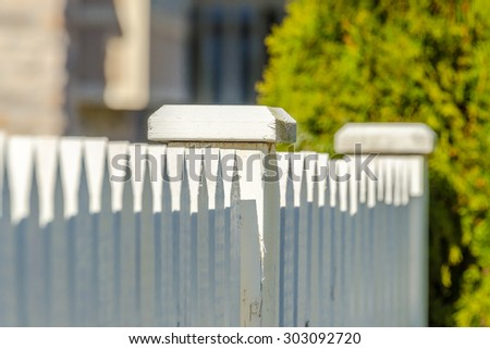 white fence with green lawn and houses. - stock photo