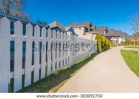 white fence with green lawn and houses.