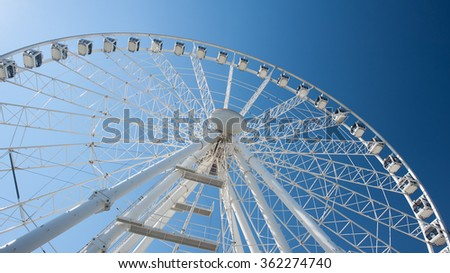 White ferris wheel against bright sun on clear blue sky background