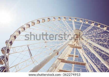 White ferris wheel on clear blue sky background, retro toned image