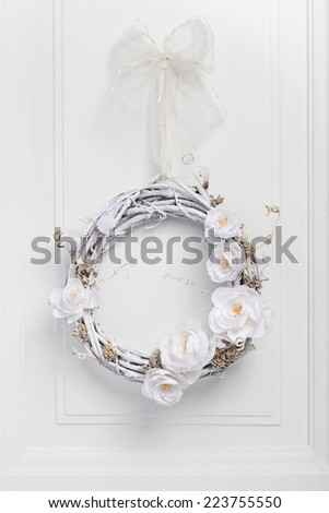 White festive twig wreath of dried vine, painted white and decorated with white paper flowers - stock photo