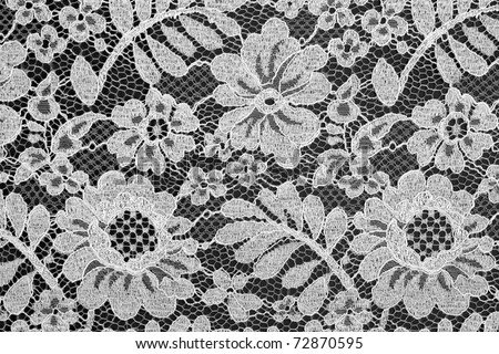 White fine lace floral texture on black background