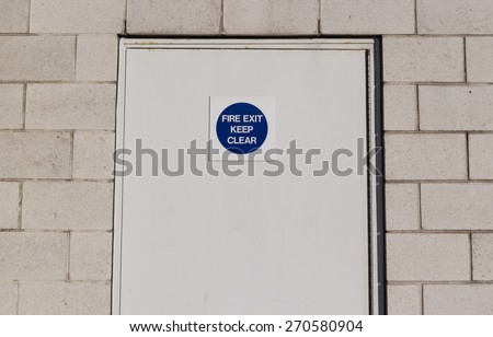 White firedoor outside with sign . Concept: Fire,building safety, - stock photo
