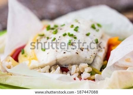 White fish fillet baked in paper, parchment with rice, vegetables, pepper, tatsy diet dish - stock photo
