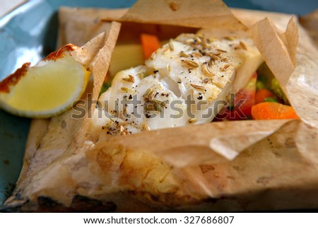 White fish fillet baked in paper, parchment with vegetables