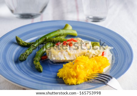 White fish with saffron rice and some cheese on top and aspargus on the side - stock photo