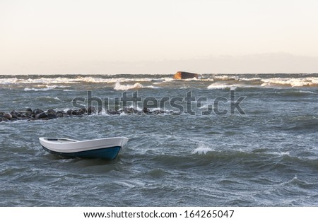 White fishing boat in stormy wavy sea