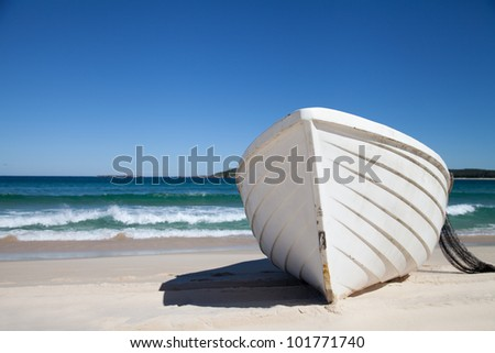 White fishing boat on sand with blue sky and water - stock photo