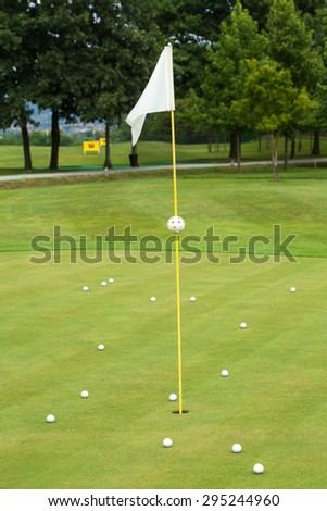 White flag on a golf course, focus on the flag - stock photo