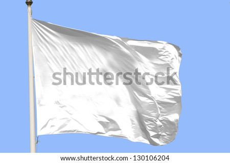 White flag waving on the wind in a blue sky - stock photo