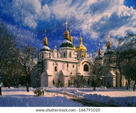 White flakes falling on the old Ukrainian monastery fell asleep paths and trails on the background, and only a sunbeam falls from the sky on the dome of an Orthodox church - stock photo