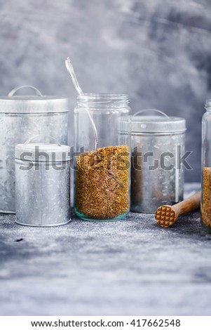 white Flax seeds glass jars with variety metal storage containers on a gray stone table. Rustic style.