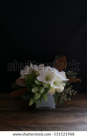 White floral arrangement of roses and amaryllis flowers on a black background.