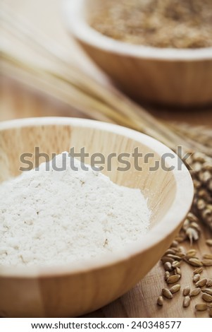 White flour and wheat on wooden table