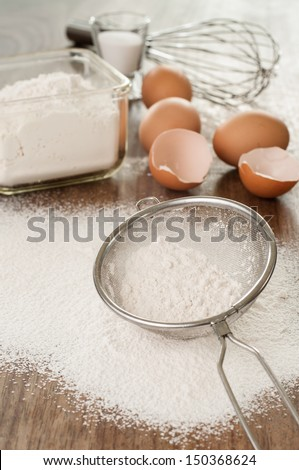 White flour in a sieve and the ingredients for baking . - stock photo
