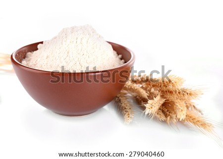 White flour in bowl and wheat ears isolated on white - stock photo