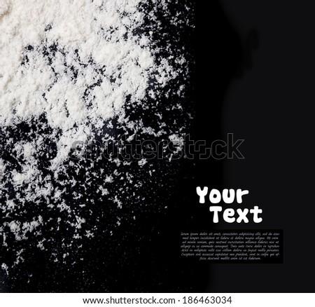 white flour sprinkled on a dark wooden table - stock photo