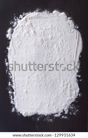 white flour sprinkled on a dark wooden table. top view - stock photo