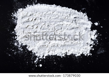 white flour sprinkled on a dark wooden table. top view