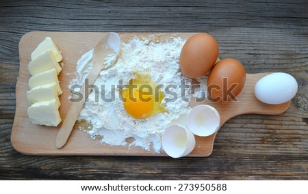 White flour with eggs, butter and wooden spoon on a cooking board - stock photo