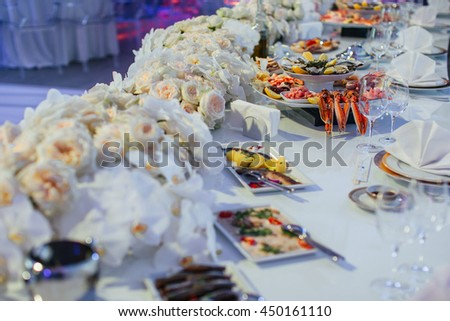 White flower garland decorates a festive dinner table - stock photo