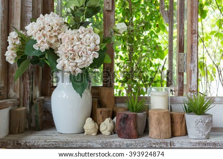 White flower vase and small succulent plants with decoration items placed on a wooden shelf near the windows in rustic atmosphere. - stock photo