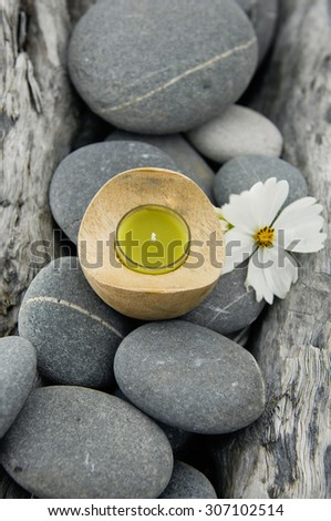 White flower  with handmade yellow candle on old wood