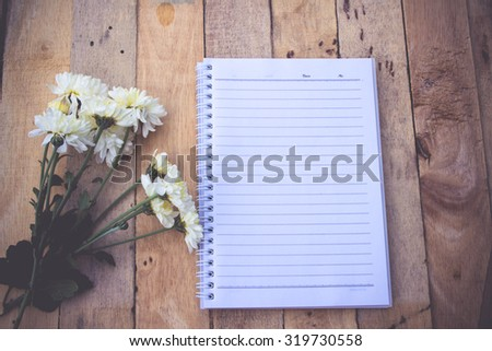 White flowers and note paper on wooden background.