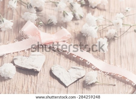 White flowers and two hearts and bow on a wooden background. Romantic card in retro style.