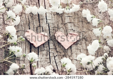 White flowers and two hearts on a wooden background. Romantic card in retro style. - stock photo