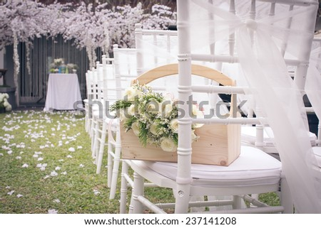 White flowers in a basket on a chair in his brother's wedding in December 2, 2014. - stock photo